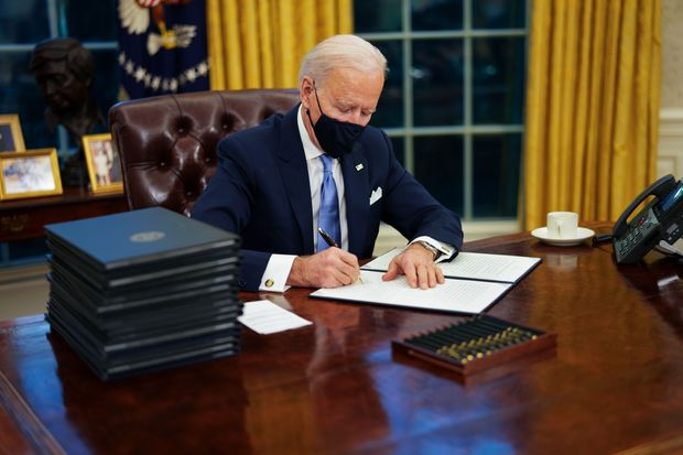 Biden signing executive orders.